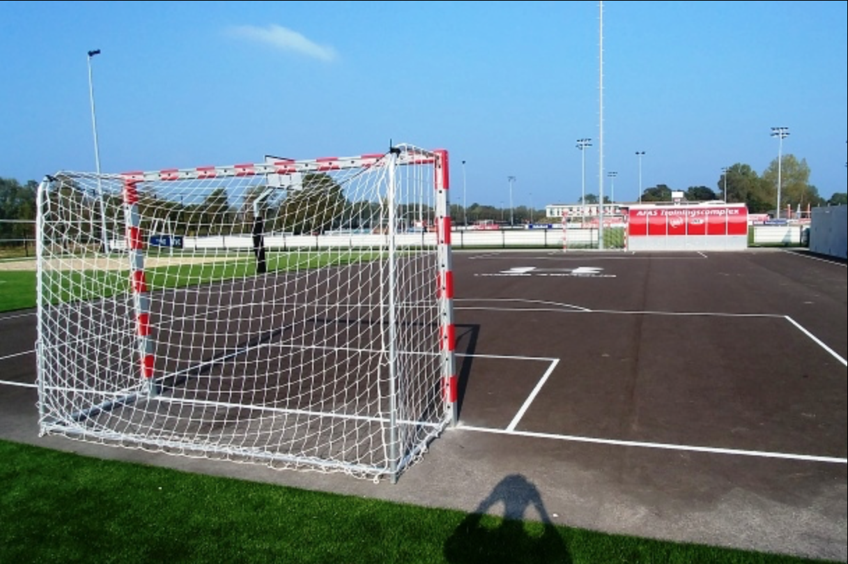 Asphalt pitch with two goals and a basketball hoop